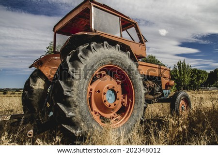 harvest, old agricultural tractor abandoned in a farm field - stock photo