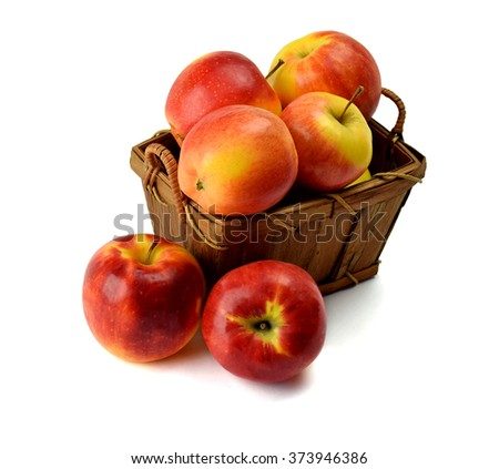 Harvest ripe delicious apples in a wooden basket isolated on white background .