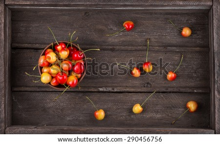 Harvest. Ripe sweet tasty cherry in an old wooden box, top view.  Breakfast for raw foodists. - stock photo