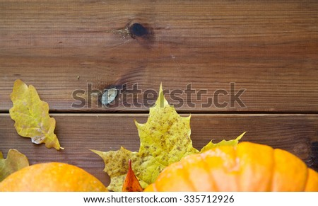 harvest, season, advertisement and autumn concept - close up of pumpkins and leaves on wooden table at home - stock photo