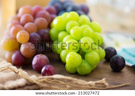 Harvest season. Fresh harvested red, black and white (green) grapes on a table, with table setting in background. - stock photo