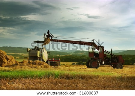 Harvest time, tractor and combine on the golden field. - stock photo