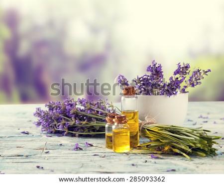Harvested lavender flowers on wooden planks, blur landscape on background - stock photo