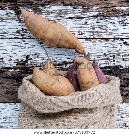 Harvested organic sweet potatoes in a hemp sack bag on rustic wood table. - stock photo