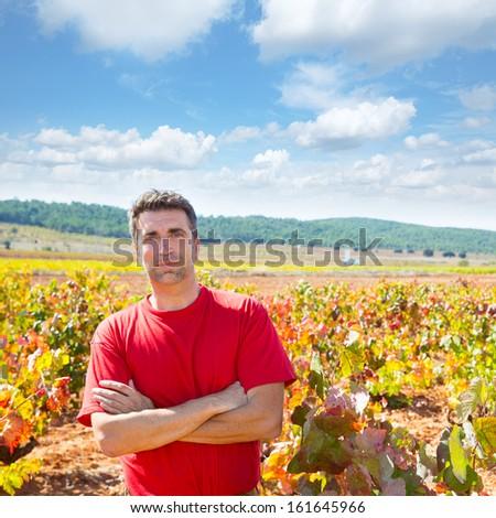 Harvester winemaker farmer proud of his vineyard in autumn golden red leaves at Mediterranean - stock photo
