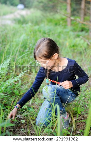 Harvests of berries and mushrooms - lovely girl pick up berries wild strawberry in the summer forest - stock photo