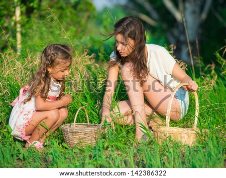 Harvests of berries and mushrooms - lovely girls with the basket of ecological harvests