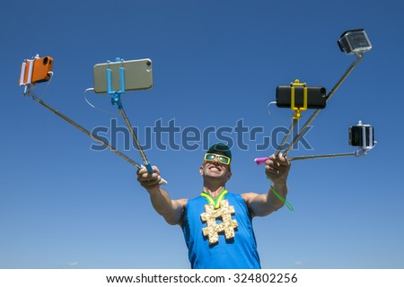Hashtag gold medal athlete smiling for his many gadgets on selfie sticks as he poses for a picture - stock photo