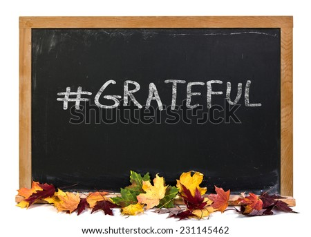 Hashtag grateful written in white chalk on a black chalkboard with fall leaves isolated on white - stock photo