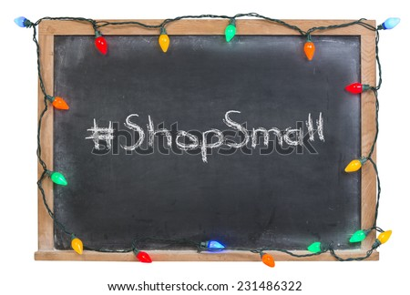 Hashtag shop small written in white chalk on a black chalkboard decorated with colored lights isolated on white - stock photo