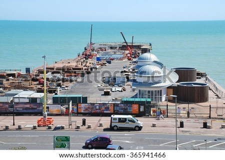 HASTINGS, ENGLAND - JULY 6, 2015: Re-construction work is carried out on the Victorian pier. Built in 1872, the pier was badly damaged by fire in October 2010 and is expected to re-open in March 2016.