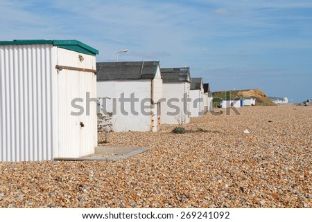HASTINGS, ENGLAND - MARCH 10, 2015: A row of traditional British beach huts at Glyne Gap in East Sussex. Such beach huts are a common sight at many seaside towns in the UK. - stock photo