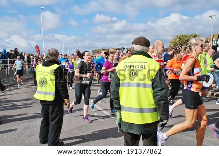 HASTINGS, ENGLAND - MARCH 23, 2014: Marshals watch runners taking part in the annual Hastings Half Marathon race. It is the 30th year the event has been held. - stock photo