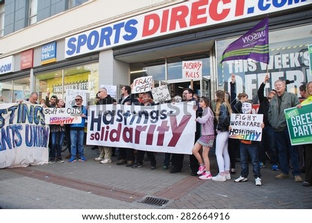 HASTINGS, ENGLAND - MAY 30, 2015: Protestors demonstrate against zero hour contracts outside a branch of the Sports Direct sports shop after an anti austerity march through the town. - stock photo