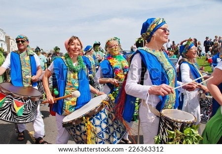 HASTINGS, ENGLAND - MAY 5, 2014: The Dende Nation samba drum troupe perform at the parade on the West Hill during the annual Jack In The Green festival. The event marks the May Day public holiday. - stock photo