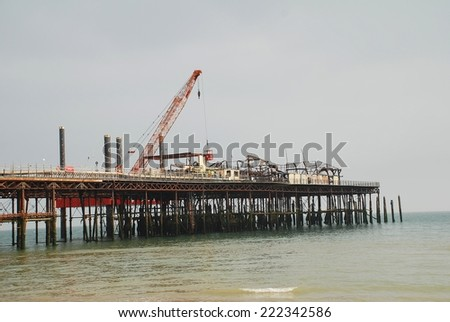 HASTINGS, ENGLAND - SEPTEMBER 20, 2014: A 39mtr crane mounted on a jack-up barge takes part in the reconstruction of the Victorian pier. Wrecked by fire in October 2010, the pier will re-open in 2015. - stock photo
