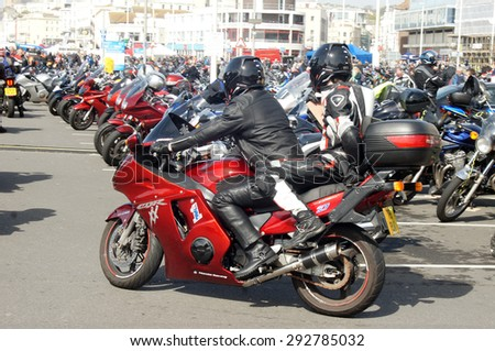 HASTINGS, UK - MAY 04, 2015: Couple in leather jacket ride their motorbike during the Biker's Festival which takes place in Hastings,UK