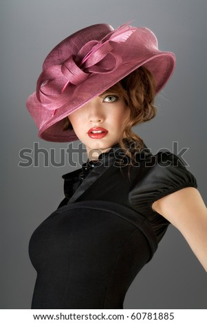 Hat and dress. A portrait of a beautiful young model in a vintage attire. - stock photo