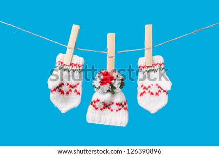 hat and pair of gloves drying in the open air hanging on clothes line affixed with wooden pegs
