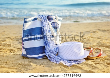 Hat, bag, sun glasses and flip flops on a sandy beach. Summer vacation concept - stock photo