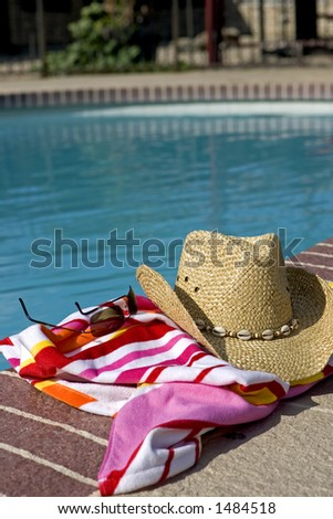 Hat, glasses and a beach towel by a pool - stock photo