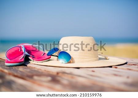 Hat, sunglasses and flip-flops against ocean - stock photo