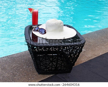 hat, sunglasses, juice by the pool - stock photo