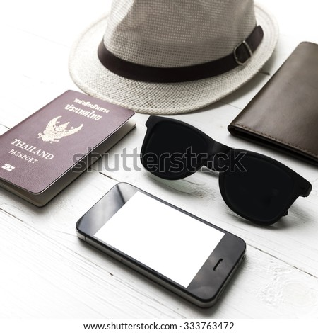 hat sunglasses smart phone and passport over white table