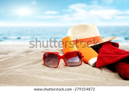 hat towel and red sunglasses on sand with suntan  - stock photo