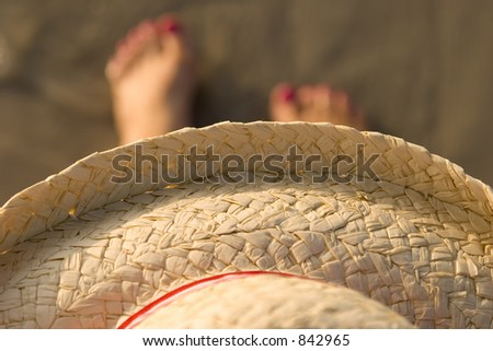 Hat with ladies feet on the sand
