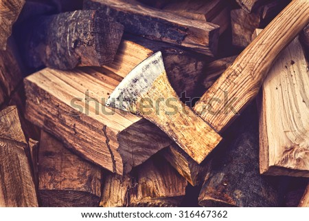 Hatchet Ax and Pile of Split Wood Logs for Fire, Selective Focus with Shallow Depth of Field, Toned Image. - stock photo