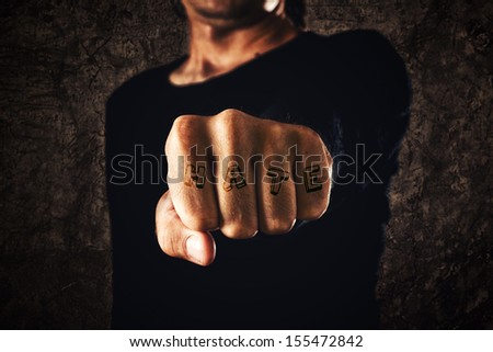 Hate. Hand with clenched fist on dark background. Power, determination, resistance concept.