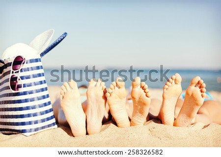 hats and summer concept - three women lying on the beach with straw hat, sunglasses and bag - stock photo
