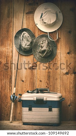 Hats hanging on wooden wall with fishing equipment - stock photo