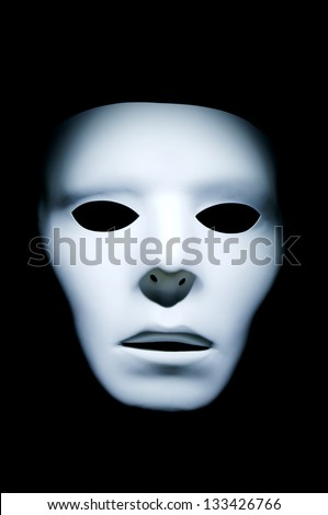 Haunting appearance of a white ghost like face against a black background. - stock photo