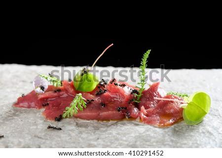 Haute cuisine, venison meat carpaccio with ants - stock photo