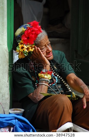 HAVANA - CIRCA FEBRUARY 2009: An unidentified elderly person sitting in a doorway, circa February 2009, in Havana. There are many poor elderly in the capital. - stock photo