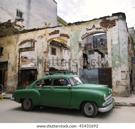 HAVANA - CIRCA NOV 2009: A green classic American car parks in street with eroded buildings circa November 2009 in Havana. Most of the old cars are used as private taxi. - stock photo