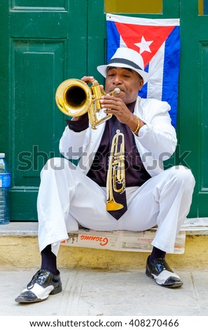 HAVANA,CUBA- APRIL 14,2016 :  Cuban musician playing the trumpet next to a cuban flag at a street in Old Havana