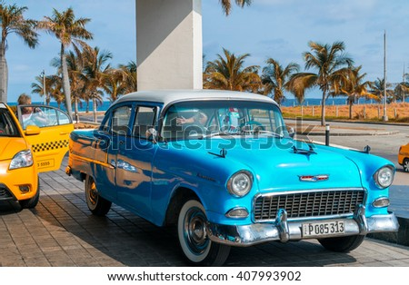 HAVANA, CUBA - APRIL 7, 2016: Old classic American cars rides in city streets. Before a new law issued on October 2011, cubans could only trade cars that were on the road before 1959. - stock photo