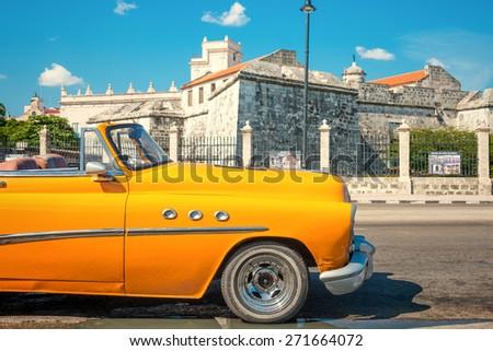 HAVANA,CUBA - APRIL 21, 2015 : Vintage american car parked next to an old colonial castle - stock photo