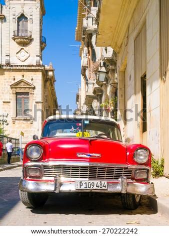 HAVANA, CUBA - APRIL 15,2015 : Vintage red car on a narrow street on the colonial neighborhood of Havana - stock photo