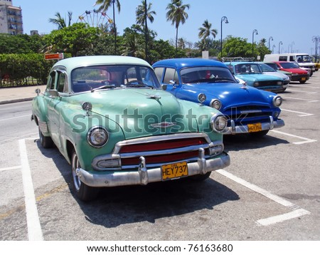HAVANA, CUBA - AUGUST, 3: Colorful classic vintage Americans cars on the Street of Havana, Cuba on August 3, 2008. More than 31,500 pre-1959 American passenger cars is still registered in Cuba. - stock photo