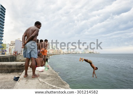 HAVANA, CUBA - CIRCA MAY, 2011: Onlookers stand watching as a young Cuban dives into the water from the Malecon sea wall.