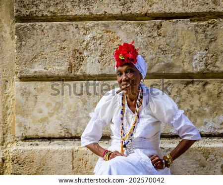 HAVANA, CUBA - DECEMBER 2, 2013: Old black lady dressed in typical cuban clothes smoking a huge cuban cigar next to the Havana Cathedral. - stock photo
