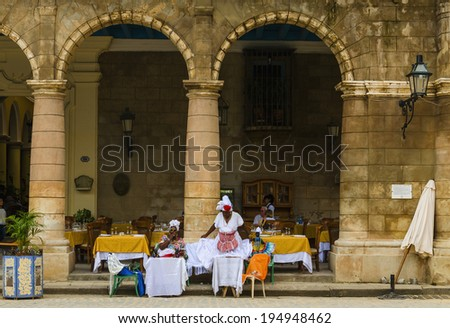 HAVANA, CUBA - DECEMBER 2, 2013: Old black ladys dressed in typical cuban clothes sitting at the front of the restaurant - it's a typical view of Havana - stock photo