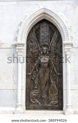 HAVANA,CUBA-FEBRUARY 8,2016:Colon cementery: angel relief sculpture at tomb door.The landmark is among the five most important in the world. It contains many valuable sculptures - stock photo