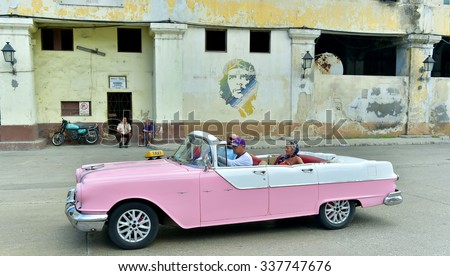 HAVANA,CUBA - FEBRUARY 28, 2015:  Old classic cars used a taxis circulating on a well known street in Havana.Havana, Cuba. Street scene with old car and worn out buildings.  - stock photo