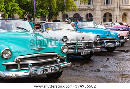 HAVANA,CUBA-FEBRUARY 9,2016:Vintage American cars parked in a line up in Central Park or Plaza. Vintage cars are both a tourist attraction and a danger to riders - stock photo