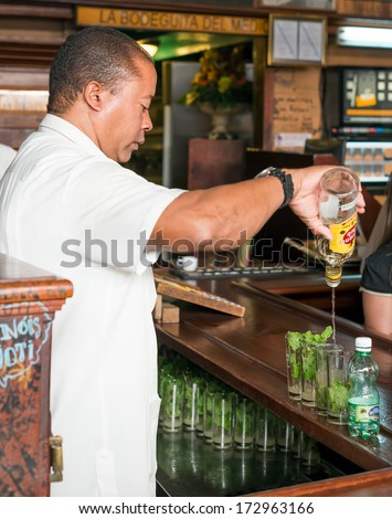 HAVANA,CUBA - JANUARY 20, 2014: Bartender preparing mojitos at La Bodeguita del Medio.This famous restaurant was a major attraction for the almost 3 million tourists who visited Cuba in 2013 - stock photo